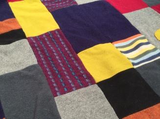 Un montón de pulóveres de lana agujereados, en una cobija.